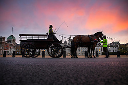 © Licensed to London News Pictures. 12/10/2020. London, UK. A horse and cart pause on Horse Guards Parade as the sunrise illuminates clouds over Whitehall. Later Prime Minister Boris Johnson will outline his plans for a three-tier system of local lockdowns to try and stop the rise of Covid-19 infections. Photo credit: Peter Macdiarmid/LNP