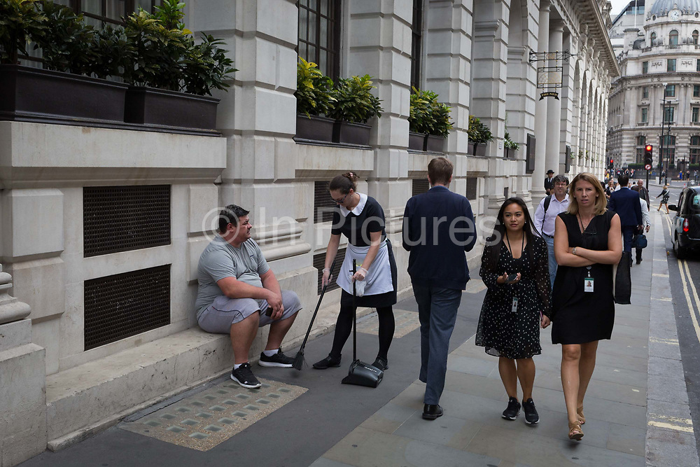 An female employee sweeps up litter from around the feet of an overweight man sitting outside The Ned Hotel in Poultry street in the City of London - the capitals financial district, on 3rd September 2018, in London England.