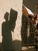 A woman sifts and sieves through sand and seeds in the streets of Djenné, Mali