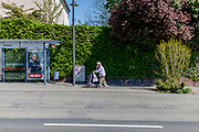 A street scene in Bad Homburg - a elderly woman with a face mask and a walking help.