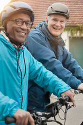 Male friends cycling and smiling on street, Bavaria, Germany