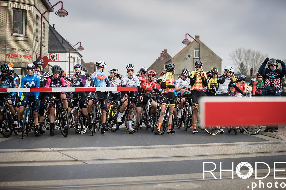 The Peloton is forced to stop at a train crossing.<br /> <br /> 13th Women's Omloop Het Nieuwsblad 2021 <br /> 1 Day Race: Gent – Ninove 124km<br /> <br /> ©Rhode.Photo
