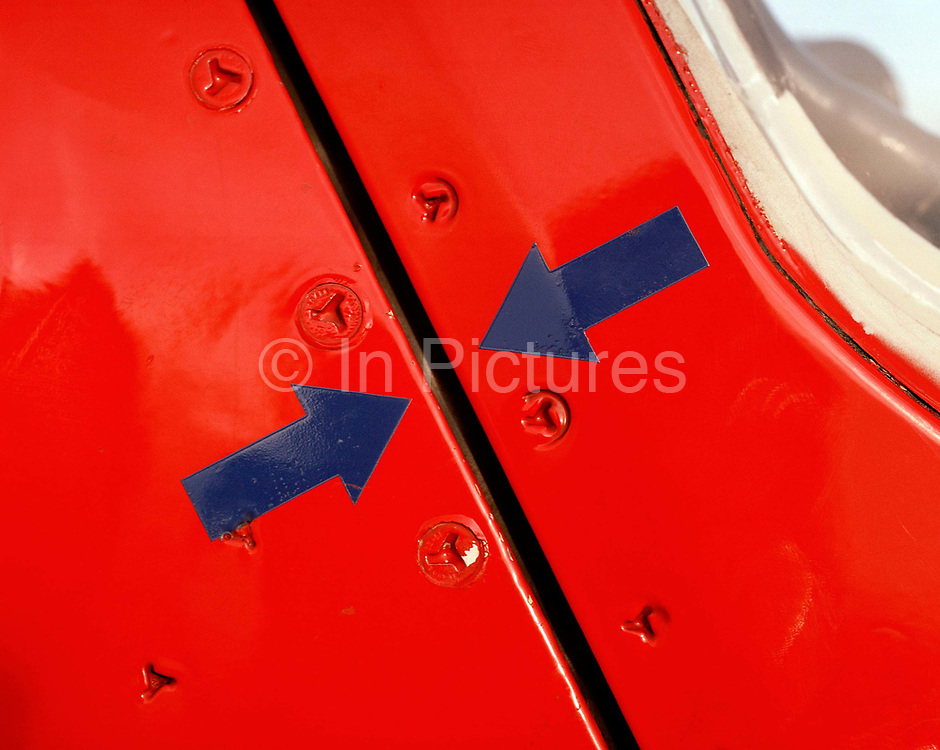 A detail of a Hawk aircraft's fuselage and canopy opening of the 'Red Arrows', Britain's Royal Air Force aerobatic team. Two blue arrows point towards each other to show that the aircraft's canopy is securely closed and ready for flight. Painted the Squadron's famous red, we can also see the rivets which can be turned by specially-designed screwdrivers that help gain access to internal technology. The Red Arrows Hawks power the team throughout their calendar of appearances at air shows and fly-pasts across the UK and a few European venues. Since 1965 the squadron have flown over 4,000 shows in 52 countries and are an important part of Britain's summer events where aerobatics aircraft perform their manoeuvres in front of massed crowds.