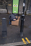 The rear of a man is seen between clothing of a man bending down to listen to his phone that is re-charging at a Duolingo Wi-fi Smart Bench at Elephant & Castle in south London, on 20th January 2021, in London, England.