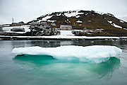 An iceberg floats in Tikhaya Bay in Franz Josef Land, Russian Arctic, in front of the abandoned Soviet polar station at Sedov Point.