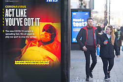 © Licensed to London News Pictures 05/02/2021.        Bexleyheath, UK. People walking past government Coronavirus Advertising. Shoppers out and about on The Broadway in Bexleyheath, South East London today as the R-rate drops below 1 in England for the first time since July last year. Photo credit:Grant Falvey/LNP