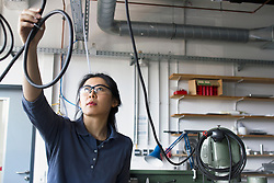 Young female engineer checking cables in an industrial plant, Freiburg im Breisgau, Baden-Wuerttemberg, Germany