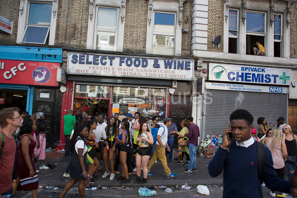 As evening draws in crowds gather outside shops and boarded up bars on Ladbroke Grove on Monday 28th August 2016 at the 50th Notting Hill Carnival in West London. A celebration of West Indian / Caribbean culture and Europes largest street party, festival and parade. Revellers come in their hundreds of thousands to have fun, dance, drink and let go in the brilliant atmosphere. It is led by members of the West Indian / Caribbean community, particularly the Trinidadian and Tobagonian British population, many of whom have lived in the area since the 1950s. The carnival has attracted up to 2 million people in the past and centres around a parade of floats, dancers and sound systems.