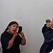 Carmen Rosa (left) and Yolanda La Amorosa prepare for their bout.in the fighters dressing room during the 'Titans of the Ring' wrestling group's Sunday performance at El Alto's Multifunctional Centre. Bolivia. The wrestling group includes the fighting Cholitas, a group of Indigenous Female Lucha Libra wrestlers who fight the men as well as each other for just a few dollars appearance money. El Alto, Bolivia, 14th March  2010. Photo Tim Clayton