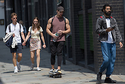 © Licensed to London News Pictures.  13/07/2021. London, UK. Members of the public walk in Shoreditch, east London as the sun comes out after a few weeks of rainy weather. Photo credit: Marcin Nowak/LNP