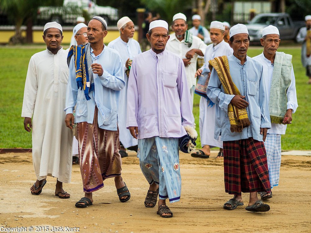 16 JUNE 2015 - CHANAE, NARATHIWAT, THAILAND: Muslim men walk to a prayer service in Chanae. About 600 people from Muslim communities in Chanae district of Narathiwat province came to the district offices Tuesday morning to participate in a prayer for peace during Ramadan. About 6,000 people have been killed in sectarian violence in Thailand's three southern provinces of Narathiwat, Pattani and Yala since a Muslim insurgency started in 2004. Attacks usually spike during religious holidays. Insurgents are fighting for more autonomy from the central government in Bangkok.        PHOTO BY JACK KURTZ