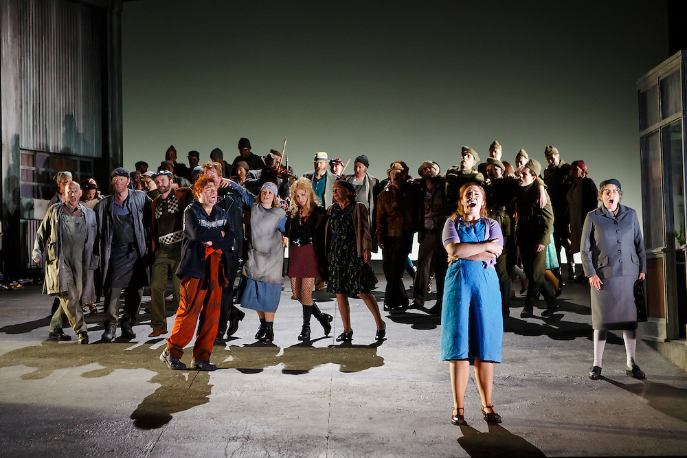 """LONDON, UK, 21 June, 2016. Laura Wilde (as Jenufa, foreground right, in blue dress) rehearses with members of the cast for the revival of director David Alden's production of Janacek's opera """"Jenufa"""" at the London Coliseum for the English National Opera. The production opens on 23 June. Photo credit: Scott Rylander."""
