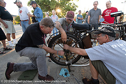 Chris Tribbey working on the back wheel of his 1911 Excelsior model-K single cylinder class-1 bike in the Motorcycle Cannonball coast to coast vintage run. Stage 5 (229 miles) from Bowling Green, OH to Bourbonnais, IL. Wednesday September 12, 2018. Photography ©2018 Michael Lichter.