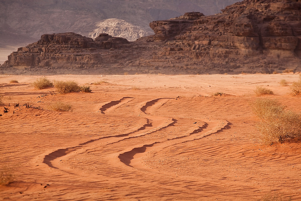 A Jeep track winds through the red sand desert of Wadi Rum, Jordan