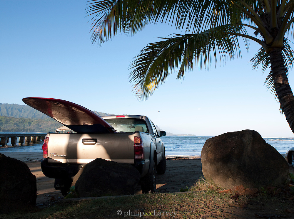 Surfers pick-up with surfboard hanging out back at a beach in Kaua'i, Hawai'i