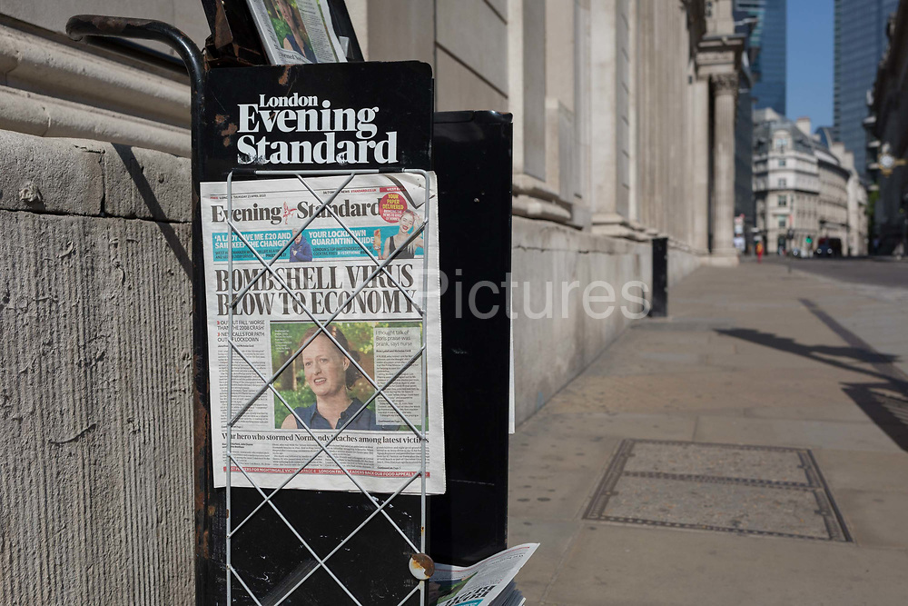 As the UK governments lockdown restrictions during the Coronavirus pandemic continues, and number of UK reported cases rose to 138,078 with a total now of 18,738 deaths, Jenny McGee, a New Zealand-born ICU nurse who treated PM Boris Johnson while in intensive care, appears on the front page of the Evening Standard newspaper alongside a bleak economic forecast, outside the Bank of England in a deserted City of London, the capitals financial district, on 23rd April 2020, in London, England.