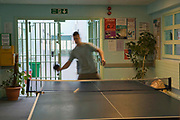 A pisoner plays table tennis during his daily recreation time on H wing at the Young Offenders Institution, Aylesbury. United Kingdom.