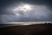 The sun breaking through storm clouds over the sea at Dungeness in Kent on the 28th of December 2021 in Dungeness, United Kingdom.