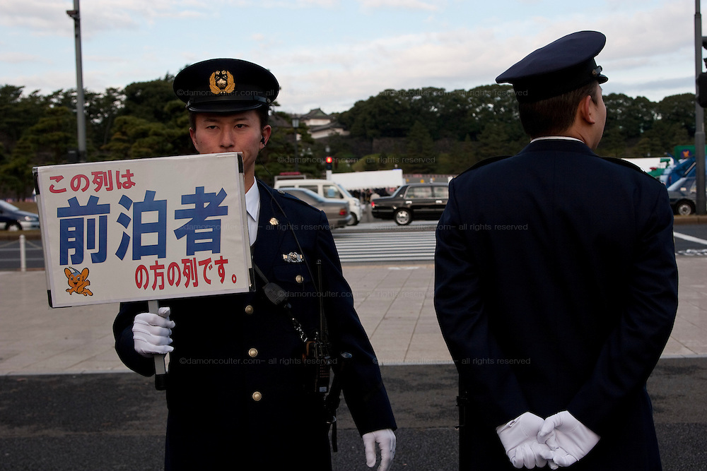 Japanese policemen using signs to control crowds in a park near the Imperial palace on the occasion of Emperor Akihito's traditional birthday address at the Royal Palace, Tokyo, Japan. December 23rd 2008