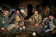 Wakhi men having diner of salty tea and bread, in a winter shepherd house. Chirog don.