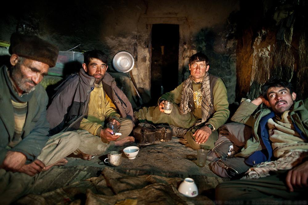 Wakhi men having diner of salty tea and bread, in a winter shepherd house. Chirog don.