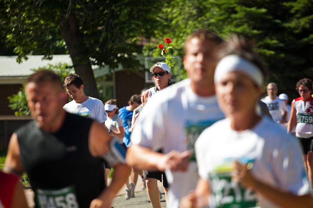 A woman competes with a flower in her hair in the 2012 Bolder Boulder 10K road race in Boulder, Colorado.