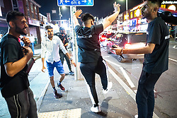 © Licensed to London News Pictures. 20/07/2021. Manchester, UK. Men dancing in the street . Muslims celebrate Eid al-Adha in Rusholme in Manchester. The festival marks the Islamic tale of the prophet Ibrahim , who offered his son as a sacrifice to Allah . Photo credit: Joel Goodman/LNP