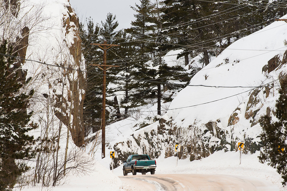 Traffic passes through a rock cut on a rural road near Marquette, Michigan in winter.