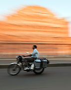 Local driving past Hawa Mahal, the Palace of Winds, in Jaipur, India