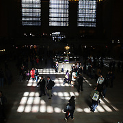 Commuters in the main concourse of Grand Central Station as the early morning light shines through the windows. Manhattan, New York, USA. 28th March 2013. Photo Tim Clayton