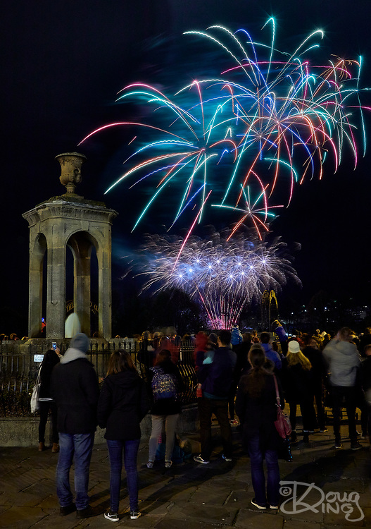 A crowd of people enjoying a fireworks display standing beside Pieroni's Fountain on Bog Island in the historic city of Bath. <br /> Bath, Avon, UK