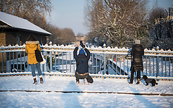 © Licensed to London News Pictures. 28/02/2018. London, UK. Members of the public stop to take pictures of the picturesque scenes at sunrise in Little Venice, West London following heavy snowfall last night. Large parts of the UK are experiencing disruption as 'Storm Emma' hits, following Russian a cold front earlier in the week named 'The Beast From The East'. Photo credit: Ben Cawthra/LNP