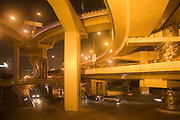 Overhead flyovers cross in this mega-junction of the Yan'an Road Central Elevated Expressway, and the Chongqing North/South Elevated Expressway. These huge motorway systems cut across and up through Shanghai creating fast routes for vehicles. The vast amounts of housing that was removed to make space for the Yan'an Expressway alone, displaced some 200,000 people, who will have been re-housed in high-rise apartment blocks in the suburbs. Their old homes would have been dwarfed by this monstrous construction of roads. Lit up at night this is a classic view of Shanghai's futuristic approach to it's massive and swift development.