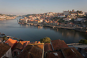 A morning aerial panorama of the city of Porto on the River Douro and a foreground of housing rooftops, on 20th July, in Porto, Portugal.