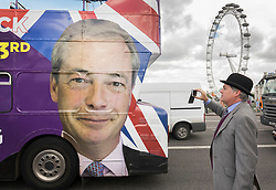 © Licensed to London News Pictures. 15/06/2016. London, UK. A man takes a phone photo of the UKIP campaign bus which displays a picture of party leader Nigel farage as Vote Leave and EU remain campaigners converge on the Thames near Parliament. Photo credit: Peter Macdiarmid/LNP