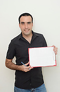 Mail Industrial Engineer in his thirties holds holds up a blank clipboard. With place to add your own text