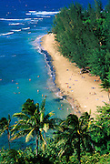 Sunbathers and blue Pacific waters at Ke'e Beach, Na Pali Coast, Island of Kauai, Hawaii