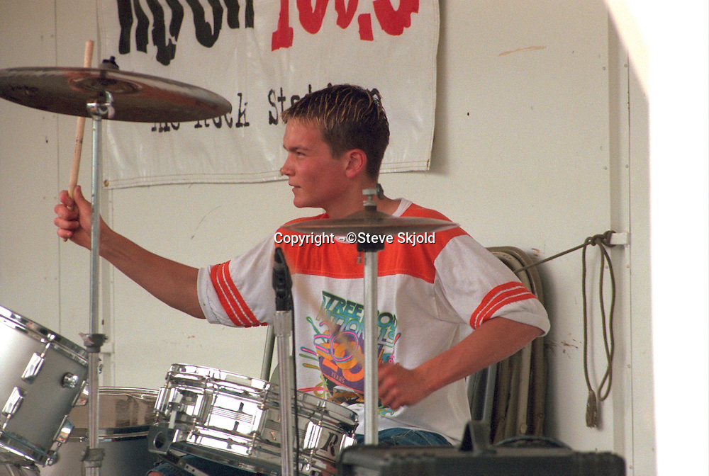 Drummer age 15 in rock and roll band jamming at Grand Old Day.  St Paul Minnesota USA