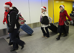 Festive travellers in a last minute Christmas getaway at Gatwick airport, Friday 23rd December 2011. Photo by: Stephen Lock / i-Images