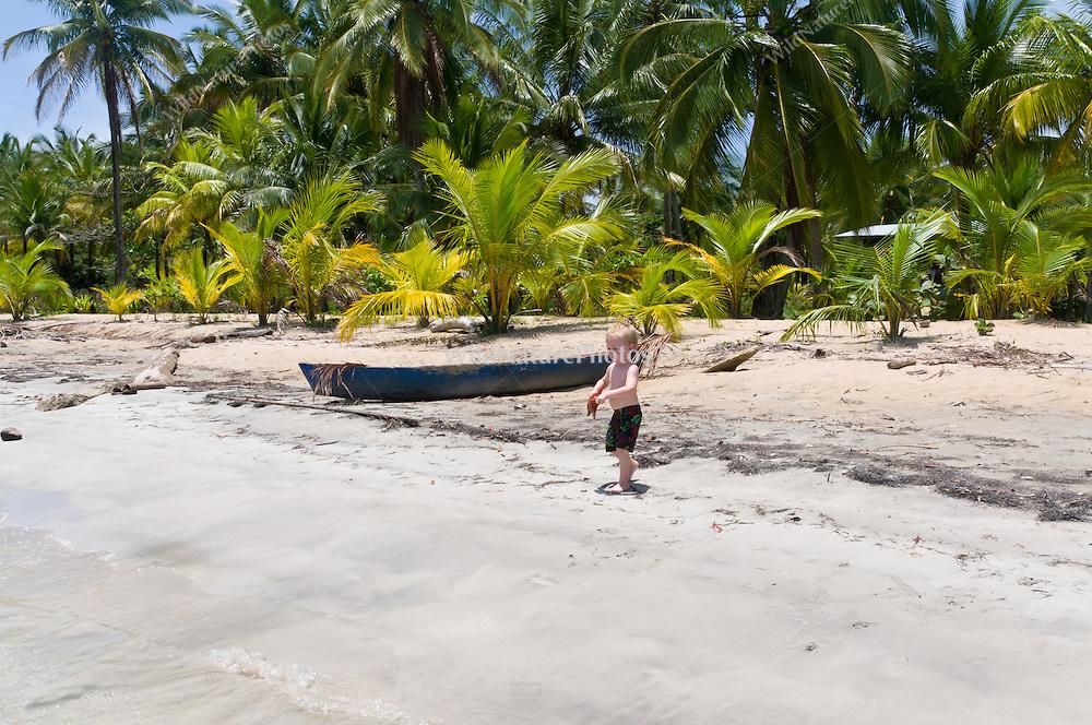 A two year old boy discovers a Cushion Sea Star (Oreaster reticulatus), a common starfish on Star Beach, near Boca del Drago, Colon Island, Panama