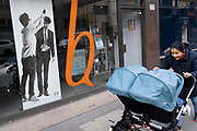 A woman pushes a double twins buggy past a barbershop window display on London Wall in the City of London, the capital's financial district, on 26th February 2021, in London, England.
