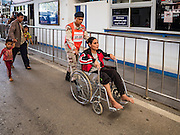 26 OCTOBER 2016 - MAE SOT, TAK, THAILAND: A Thai defense volunteer helps a Burmese woman in a wheelchair to the border in Mae Sot for her repatriation from the Nupo Temporary Shelter refugee camp. Sixtyfive Burmese refugees living in the Nupo Temporary Shelter refugee camp in Tak Province of Thailand were voluntarily repatriated to Myanmar. About 11,000 people live in the camp. The repatriation was the first large scale repatriation of Myanmar refugees living in Thailand. Government officials on both sides of the Thai / Myanmar border said the repatriation was made possible by recent democratic reforms in Myanmar. There are approximately 150,000 Burmese refugees living in camps along the Thai / Myanmar border. The Thai government has expressed interest several times in the last two years in starting the process of repatriating the refugees.      PHOTO BY JACK KURTZ