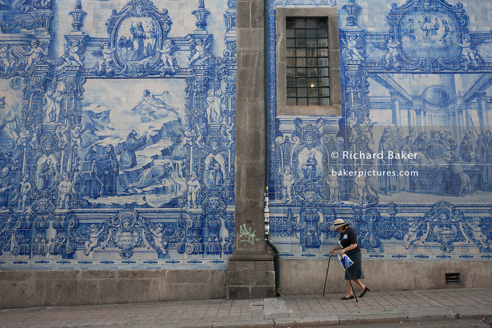 A lady struggles with sticks beneath traditional Azulejo tiles on the wall of Capela Das Almas (church), on Rua Santa Catarina Porto, Portugal. The panels depict scenes from the lives of various saints including the death of St Francis and the martyrdom of St Catherine. Eduardo Leite painted the tiles in a classic 18th-century style, though they actually date back only to the early 20th century.