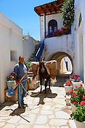Farmer with donkey in the narrow streets of  Komiaki Hill village