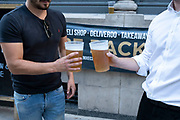 On the day that it was announced that the Coronavirus lockdown measures are set to ease even further, two drinkers pose for a photograph outside a pub in the City of London enjoy some take out drinks at The Phoenix pub on 23rd June 2020 in London, England, United Kingdom. The government has relaxed its lockdown rules, and from early July is allowing spubs to reopen, as long as they have set up social distancing systems.