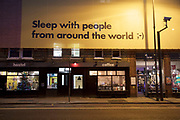 Sleep with people from around the World, multicultural message on a hoarding in London, England, United Kingdom.