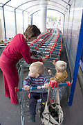 Mom placing coin in slot to unlock grocery basket at Tesco supermarket. Balucki District Lodz Central Poland