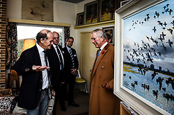 The Prince of Wales speaks with Falcon Scott (front left), grandson of explorer Robert Falcon Scott, as they take a tour around his father Sir Peter Scott's house, during a visit to the Wildfowl and Wetlands Trust's Slimbridge Wetland Centre in Gloucestershire to celebrate its 70th anniversary.