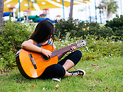 Young female teen enjoys a sunny winter day at the park while playing a guitar