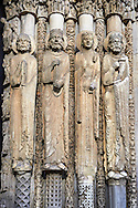 .West Facade, central Portal c. 1145,  Cathedral of Notre Dame, Chartres, France. Gothic statues of four elongated human figures with halos. The leftmost is a bearded man holding a book. The next is a crowned man with long hair and a beard also holding a book. The next is a crowned female with elaborate garments. The rightmost is a bearded, crowned man holding a scroll. Some scholars believe that the jamb figures are the ancestors of Christ.. A UNESCO World Heritage Site. . .<br /> <br /> Visit our MEDIEVAL ART PHOTO COLLECTIONS for more   photos  to download or buy as prints https://funkystock.photoshelter.com/gallery-collection/Medieval-Middle-Ages-Art-Artefacts-Antiquities-Pictures-Images-of/C0000YpKXiAHnG2k